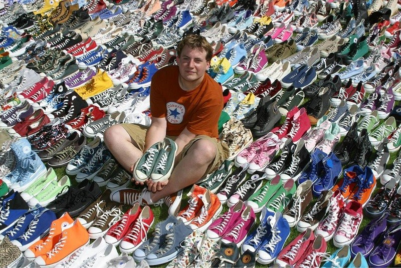 fan de converse assis sur un collection de sneakers